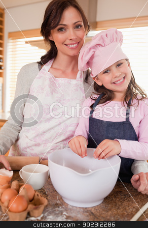 Portrait of a mother baking with her daughter stock photo, Portrait of a mother baking with her daughter in a kitchen by Wavebreak Media