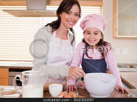 Mother baking with her daughter stock photo, Mother baking with her daughter in a kitchen by Wavebreak Media