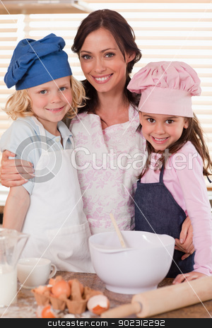 Portrait of a mother and her children baking stock photo, Portrait of a mother and her children baking in a kitchen by Wavebreak Media