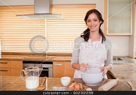Smiling woman baking stock photo, Smiling woman baking in her kitchen by Wavebreak Media