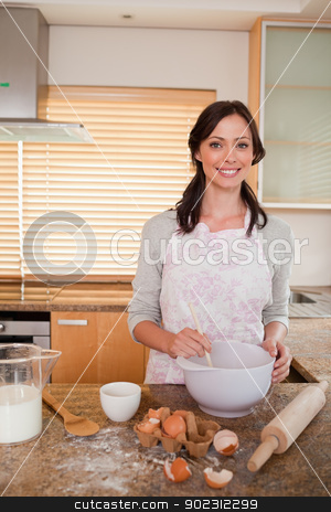Portrait of a woman baking stock photo, Portrait of a woman baking in her kitchen by Wavebreak Media