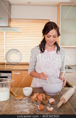 Portrait of a smiling woman baking stock photo, Portrait of a smiling woman baking in a kitchen by Wavebreak Media