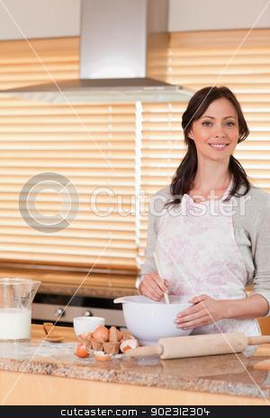 Portrait of a beautiful woman baking stock photo, Portrait of a beautiful woman baking in her kitchen by Wavebreak Media