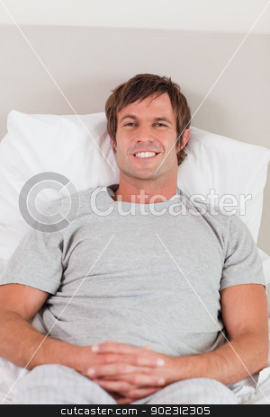 Portrait of a man lying on his bed stock photo, Portrait of a man lying on his bed while looking at the camera by Wavebreak Media