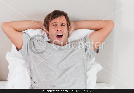 Handsome man yawning stock photo, Handsome man yawning in his bedroom by Wavebreak Media