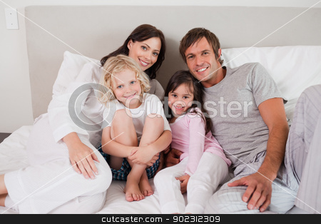 Smiling family posing on a bed stock photo, Smiling family posing on a bed while looking at the camera by Wavebreak Media
