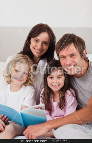 Portrait of a happy family reading a book stock photo, Portrait of a happy family reading a book in a bedroom by Wavebreak Media