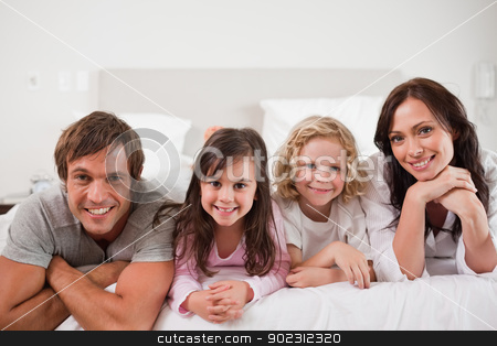 Happy family lying in a bed stock photo, Happy family lying in a bed together by Wavebreak Media