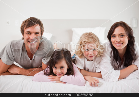 Smiling family lying in a bed stock photo, Smiling family lying in a bed together by Wavebreak Media