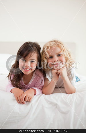 Portrait of children lying on their bellies stock photo, Portrait of children lying on their bellies in a bedroom by Wavebreak Media