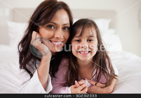 Mother and her daughter lying on a bed stock photo, Mother and her daughter lying on a bed while looking at the camera by Wavebreak Media