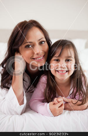 Portrait of a mother and her daughter lying on a bed stock photo, Portrait of a mother and her daughter lying on a bed while looking at the camera by Wavebreak Media