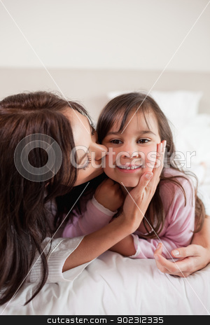 Portrait of a mother kissing her daughter stock photo, Portrait of a mother kissing her daughter in a bedroom by Wavebreak Media