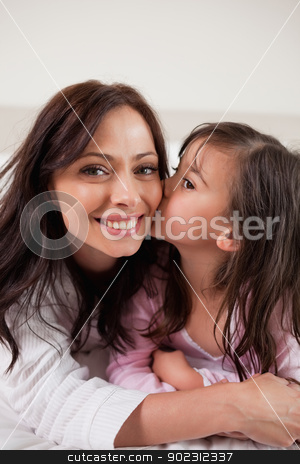 Portrait of a girl kissing her mother stock photo, Portrait of a girl kissing her mother in a bedroom by Wavebreak Media