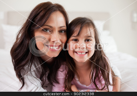 Girl and her mother lying on a bed stock photo, Girl and her mother lying on a bed while looking at the camera by Wavebreak Media