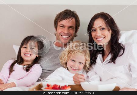 Family having breakfast together stock photo, Family having breakfast together in a bedroom by Wavebreak Media