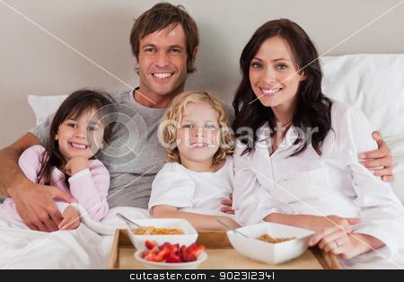 Happy family having breakfast together stock photo, Happy family having breakfast together in a bedroom by Wavebreak Media