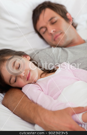 Portrait of a father sleeping with his daughter stock photo, Portrait of a father sleeping with his daughter in a bedroom by Wavebreak Media