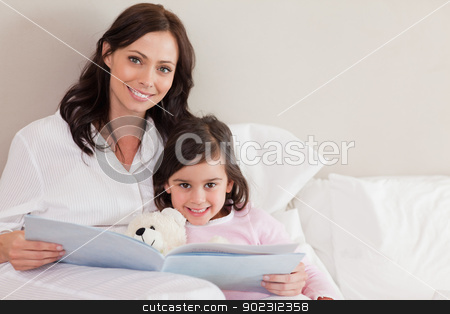 Happy mother reading a story to her daughter stock photo, Happy mother reading a story to her daughter in a bedroom by Wavebreak Media