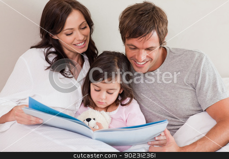 Happy parents reading a story to their daughter stock photo, Happy parents reading a story to their daughter in a bedroom by Wavebreak Media