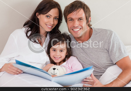 Smiling parents reading a story to their daughter stock photo, Smiling parents reading a story to their daughter in a bedroom by Wavebreak Media