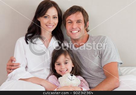 Parents posing with their daughter stock photo, Parents posing with their daughter in a bedroom by Wavebreak Media