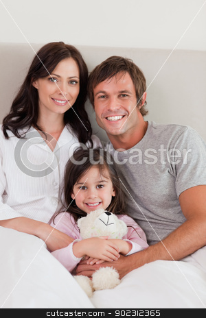 Portrait of parents posing with their daughter stock photo, Portrait of parents posing with their daughter in their bedroom by Wavebreak Media