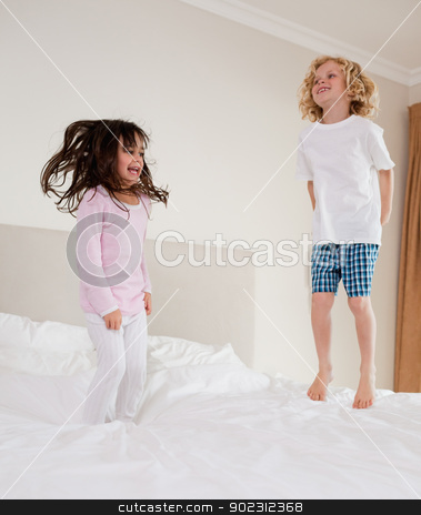 Portrait of children jumping stock photo, Portrait of children jumping on a bed  by Wavebreak Media