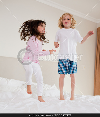 Portrait of siblings jumping stock photo, Portrait of siblings jumping on a bed by Wavebreak Media