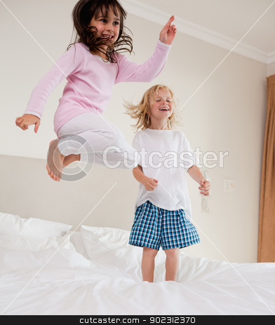 Portrait of playful siblings jumping stock photo, Portrait of playful siblings jumping on a bed by Wavebreak Media