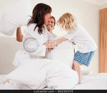 Cheerful family having pillow fight stock photo, Cheerful family having pillow fight in a bedroom by Wavebreak Media