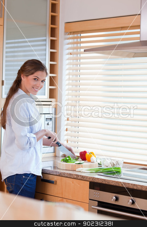 Portrait of a happy woman slicing pepper stock photo, Portrait of a happy woman slicing pepper in her kitchen by Wavebreak Media
