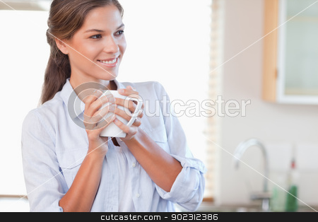 Smiling woman holding a cup of tea stock photo, Smiling woman holding a cup of tea in her kitchen by Wavebreak Media