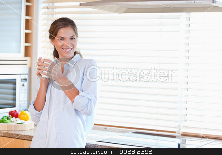 Happy woman holding a cup of tea stock photo, Happy woman holding a cup of tea in her kitchen by Wavebreak Media