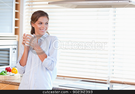 Happy woman holding a cup of coffee stock photo, Happy woman holding a cup of coffee in her kitchen by Wavebreak Media