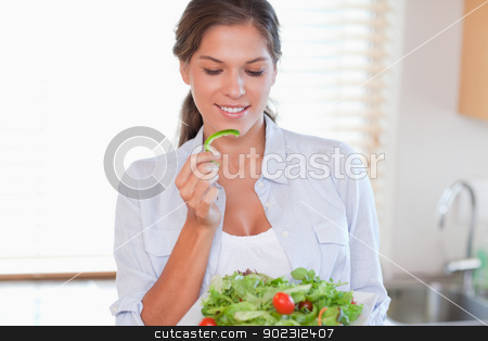 Woman eating a salad stock photo, Woman eating a salad in her kitchen by Wavebreak Media