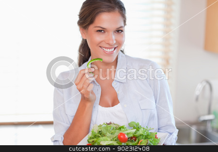 Smiling woman eating a salad stock photo, Smiling woman eating a salad in her kitchen by Wavebreak Media
