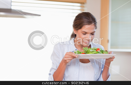 Woman smelling a salad stock photo, Woman smelling a salad in her kitchen by Wavebreak Media