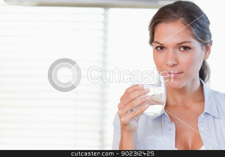 Woman drinking a glass of water stock photo, Woman drinking a glass of water in her kitchen by Wavebreak Media