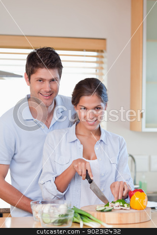 Portrait of a couple cooking stock photo, Portrait of a couple cooking in their kitchen by Wavebreak Media
