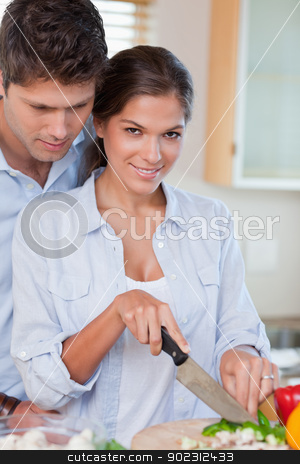 Portrait of a young couple cooking stock photo, Portrait of a young couple cooking in their kitchen by Wavebreak Media