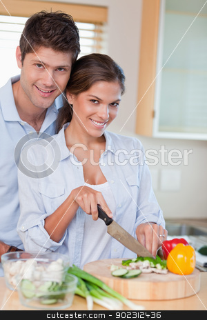Portrait of a married couple cooking stock photo, Portrait of a married couple cooking in their kitchen by Wavebreak Media