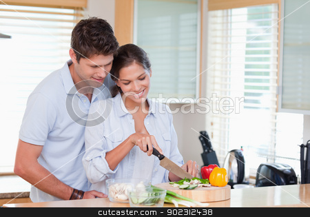 Happy couple cooking stock photo, Happy couple cooking in their kitchen by Wavebreak Media