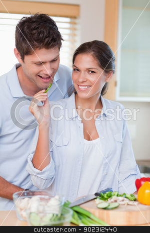 Portrait of a beautiful couple cooking stock photo, Portrait of a beautiful couple cooking in their kitchen by Wavebreak Media