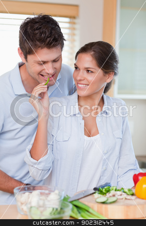 Portrait of a smiling couple cooking stock photo, Portrait of a smiling couple cooking in their kitchen by Wavebreak Media