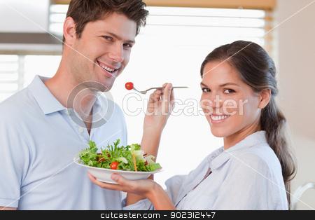 Housewife feeding her husband stock photo, Housewife feeding her husband in their kitchen by Wavebreak Media