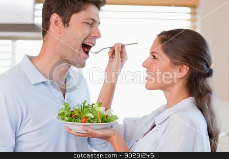 Accomplice couple tasting a salad stock photo, Accomplice couple tasting a salad in their kitchen by Wavebreak Media
