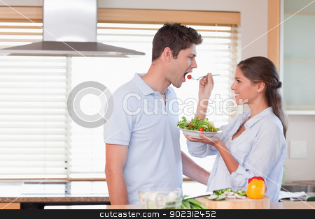 Happy couple tasting a salad stock photo, Happy couple tasting a salad in their kitchen by Wavebreak Media