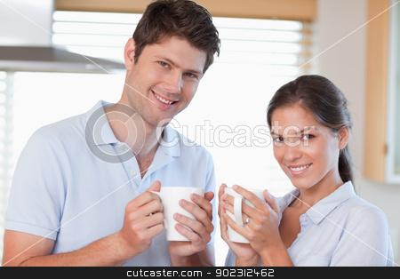 Happy couple drinking coffee stock photo, Happy couple drinking coffee in their kitchen by Wavebreak Media