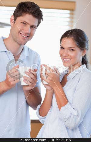 Portrait of a couple drinking coffee stock photo, Portrait of a couple drinking coffee in their kitchen by Wavebreak Media